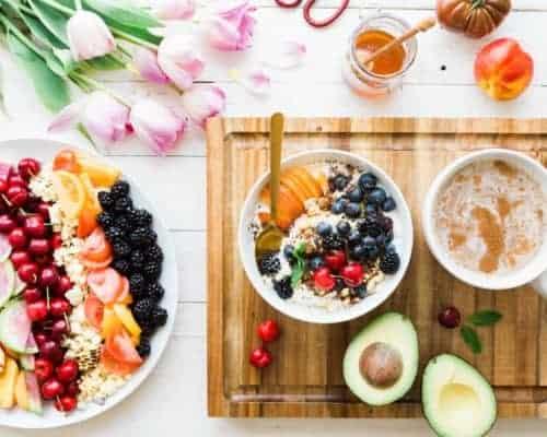 Ein Frühstück mit Müsli, Honig, vielen verschieben Früchten und Avocado