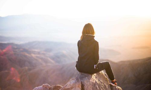 Frau sitzt bei Sonnenaufgang auf einer Bergspitze