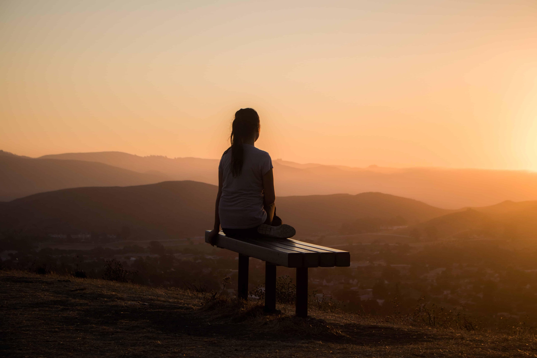 Frau entspannt bei Sonnenaufgang auf einer Bank