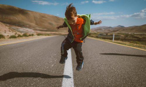 Kind hüpft glücklich auf der Straße