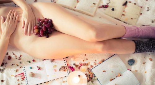 Frau liegt nackt mit Büchern und Kerze auf einem Bett und bedeckt ihre Scham mit Weintrauben
