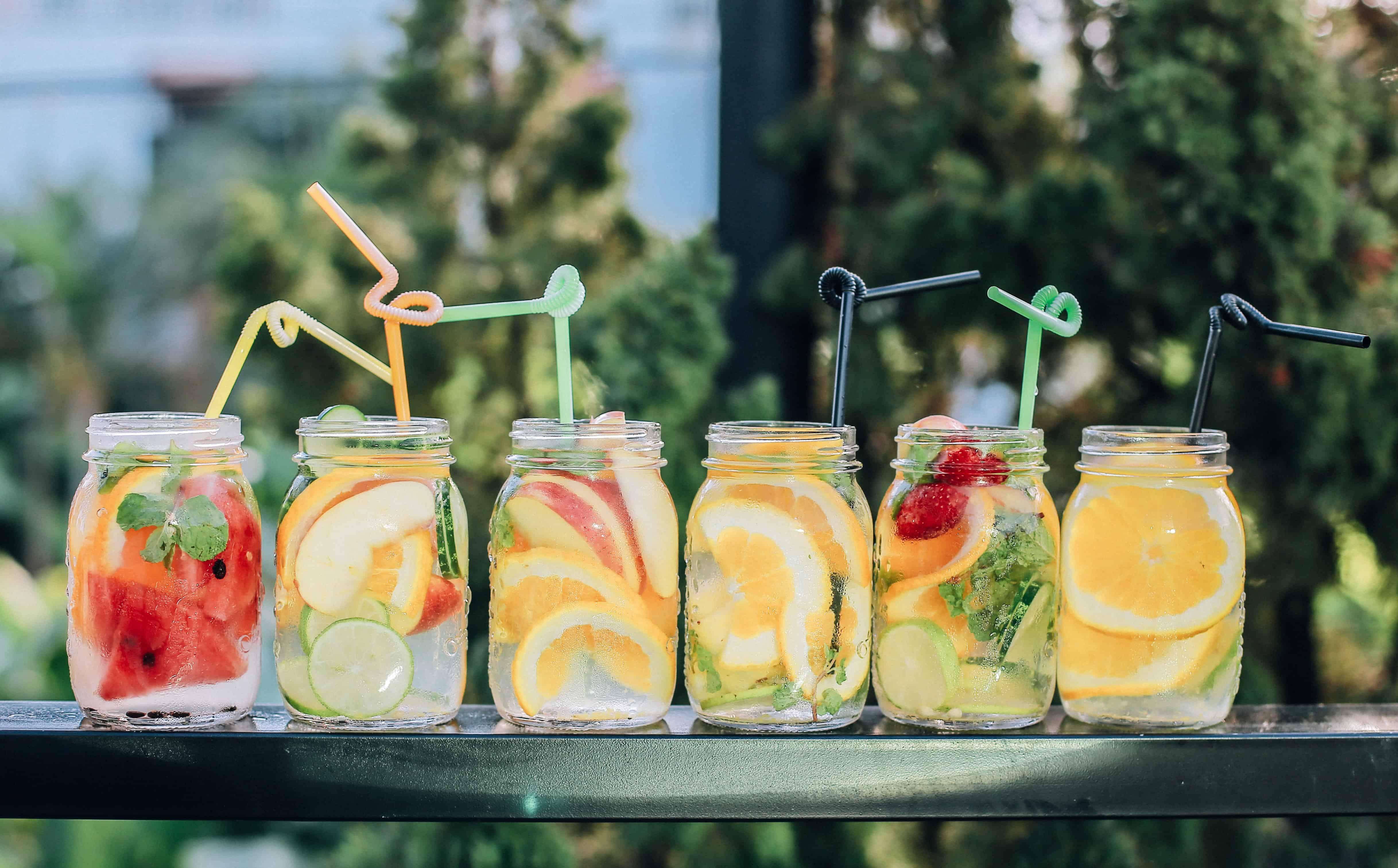 Sechs Einmachgläser mit Früchten aromatisiertem Wasser und Strohalmen