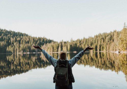 Frau steht am See und streckt die Arme in die Höhe