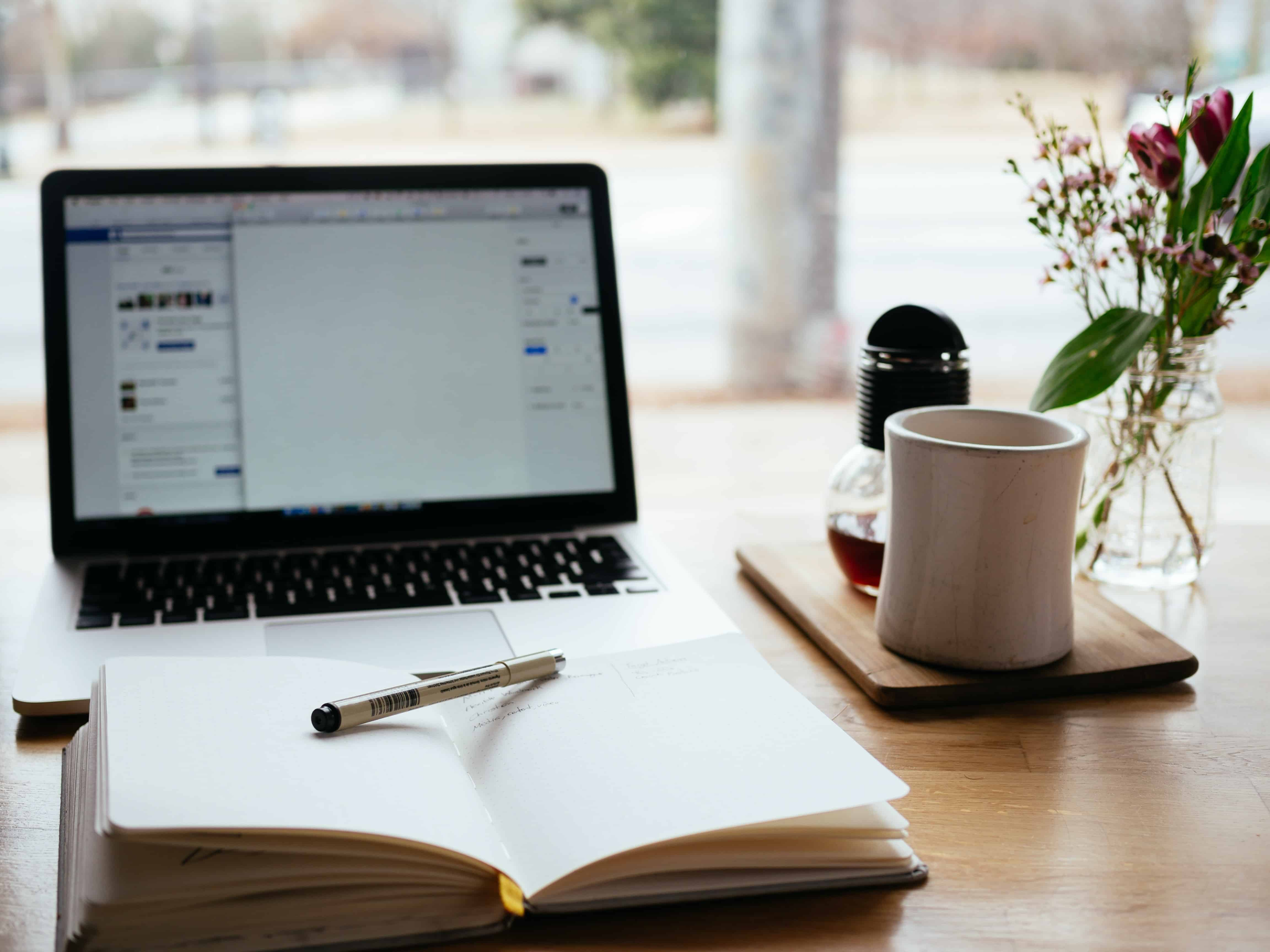 Laptop, Buch, Stift, Tee und Blumen