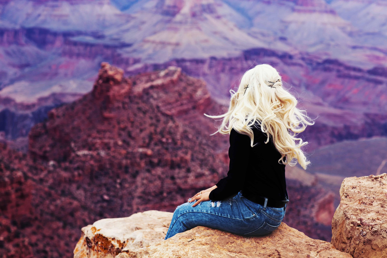Eine Frau sitzt auf einem Felsen und schaut in die Ferne