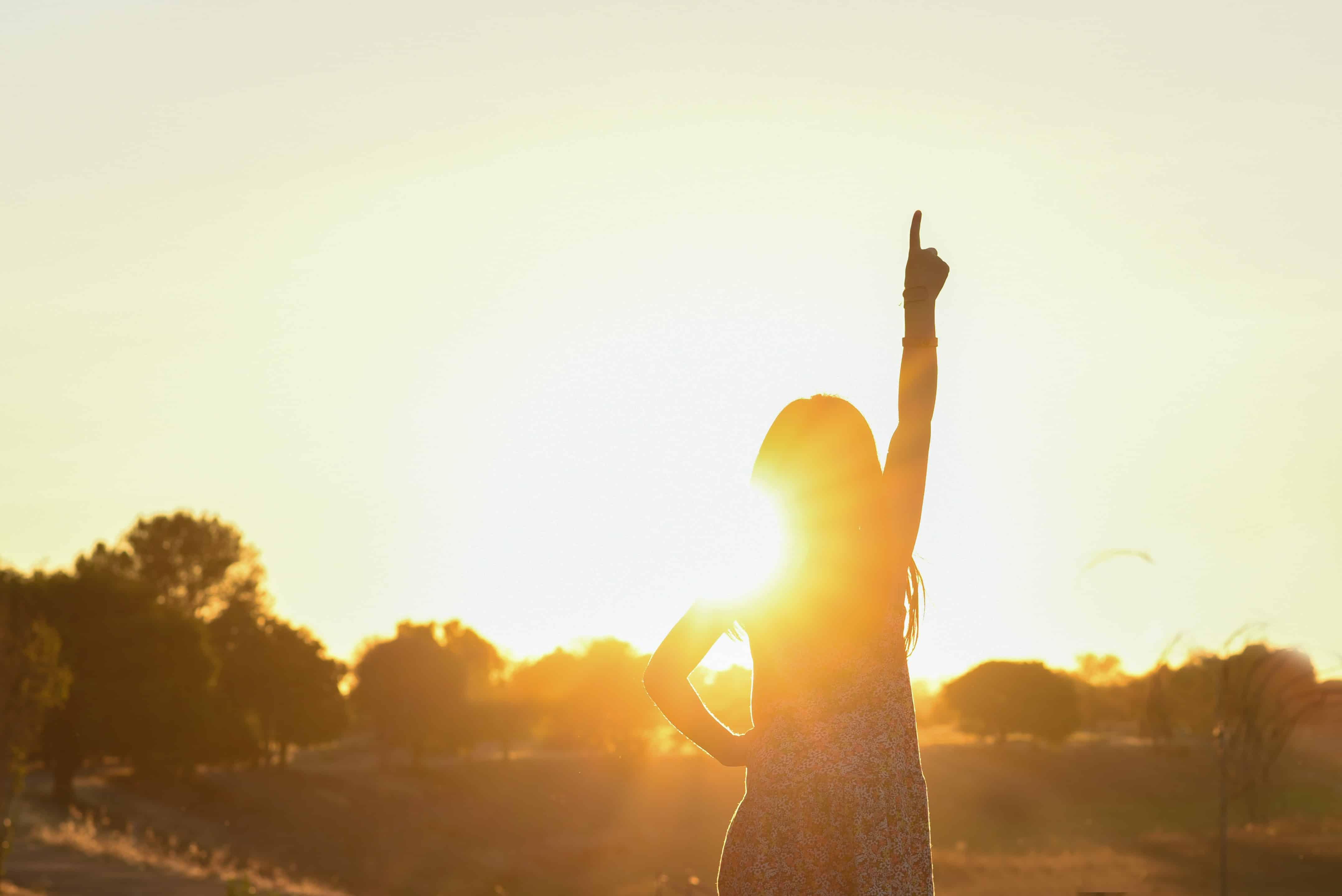 Frau zeigt auf in Sonnenaufgang