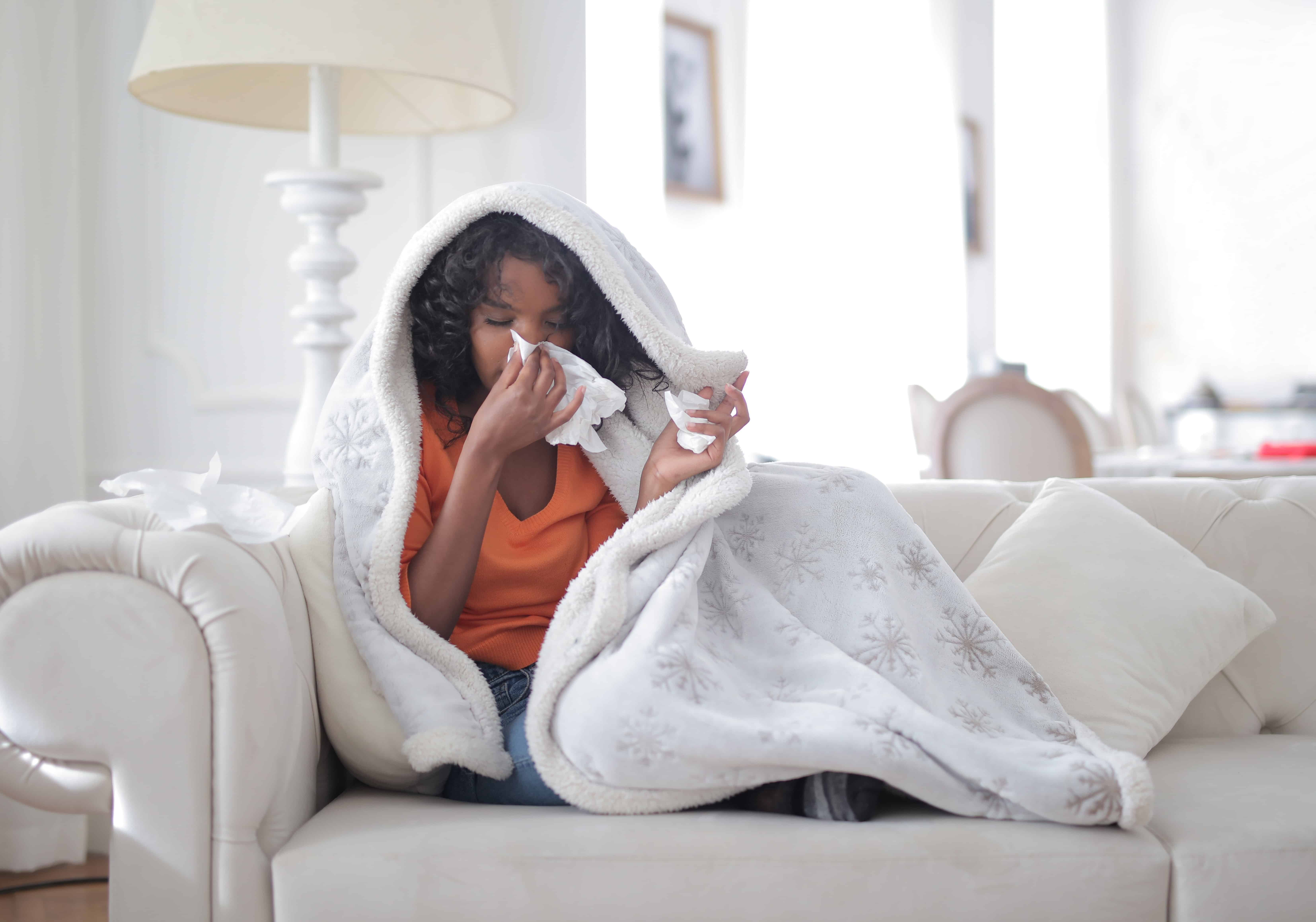 Frau auf Sofa unter Wolldecke putzt sich die Nase