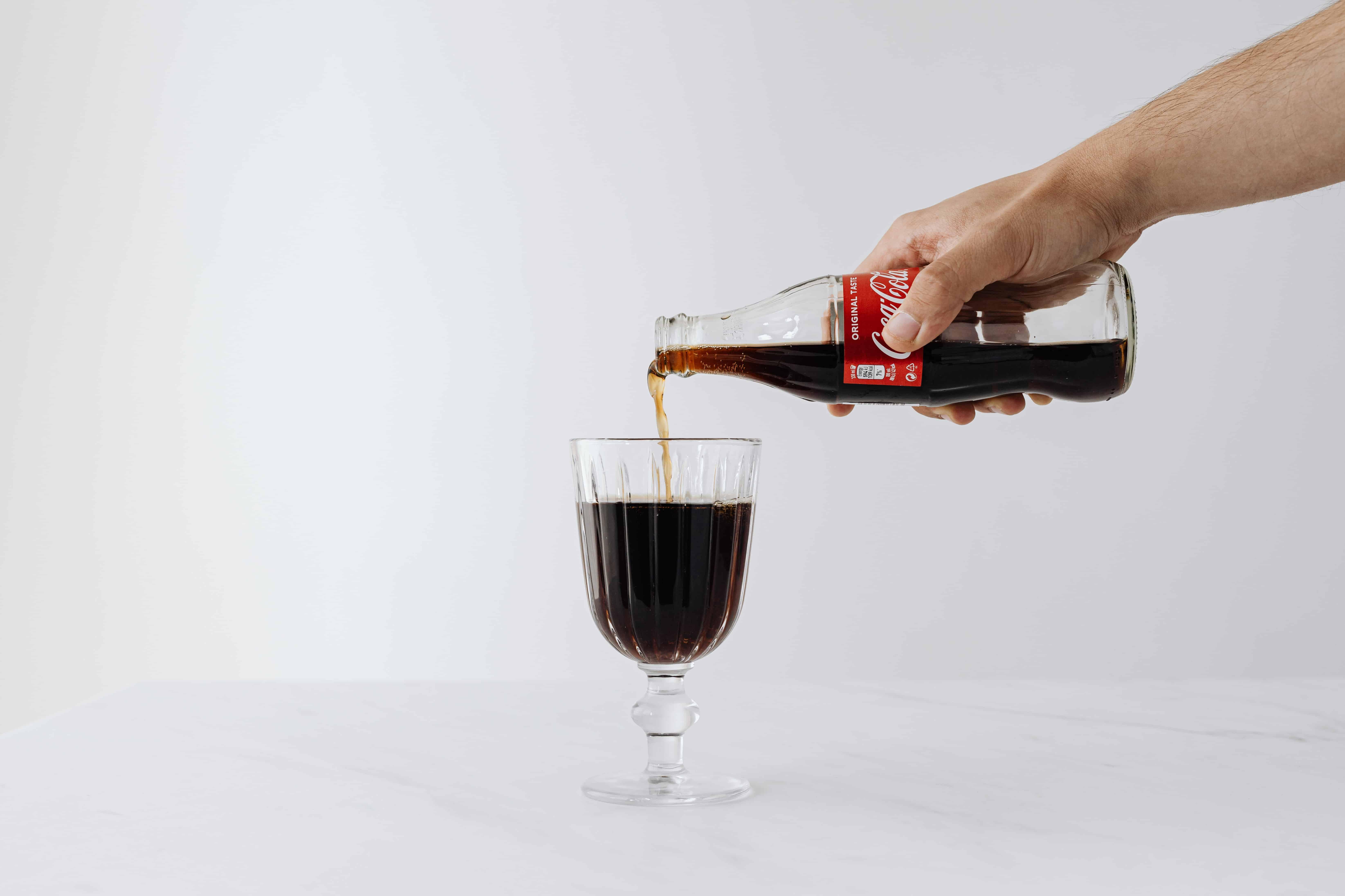 Glas Coca Cola wird eingeschenkt