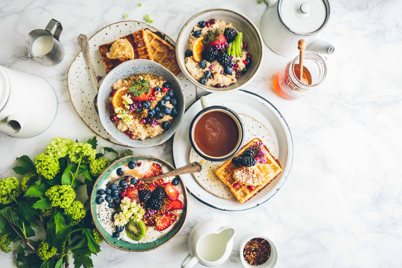 Frühstückstisch mit Waffeln und Porridge mit Obst