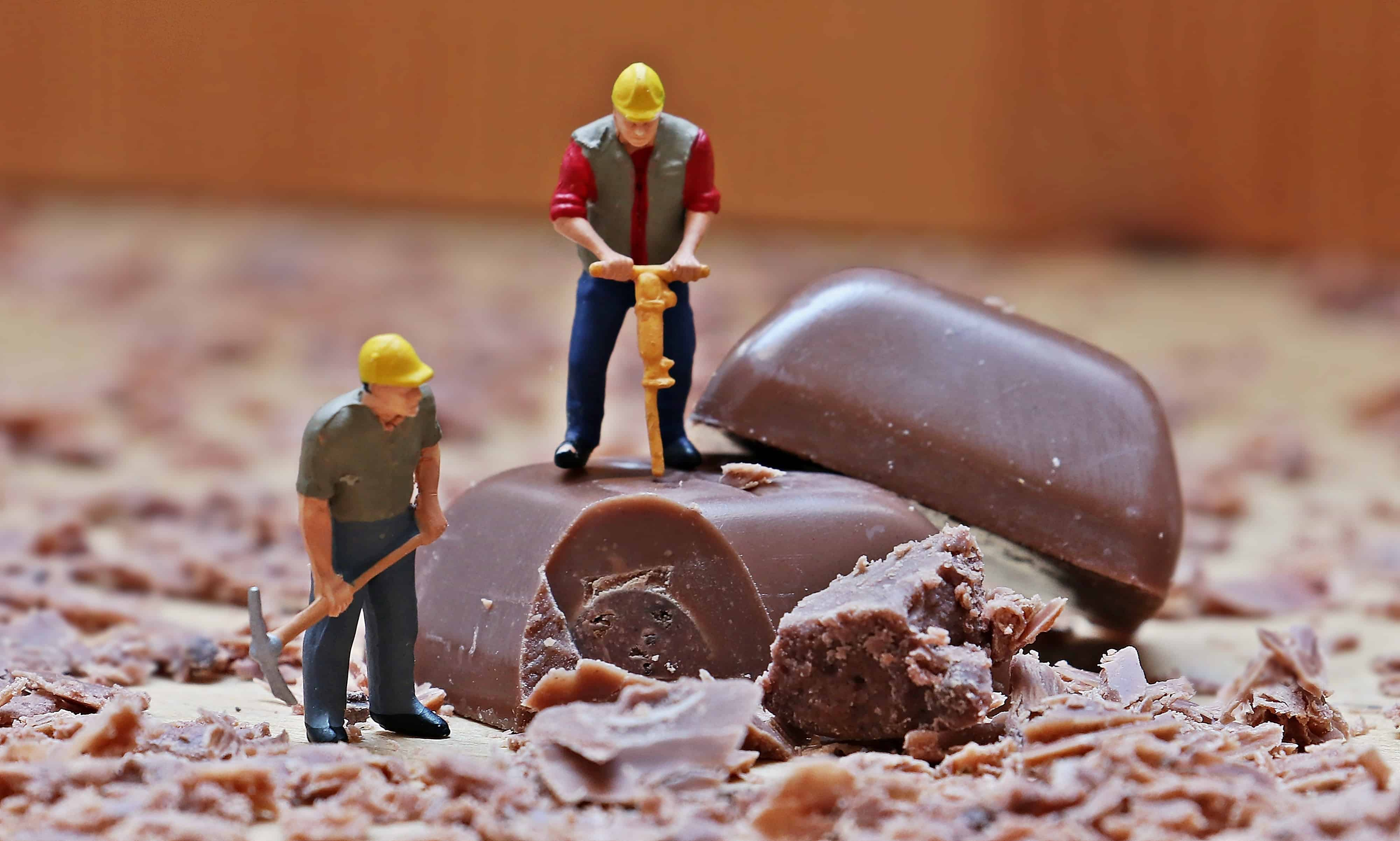 Minibauarbeiter bearbeiten Stück Schokolade