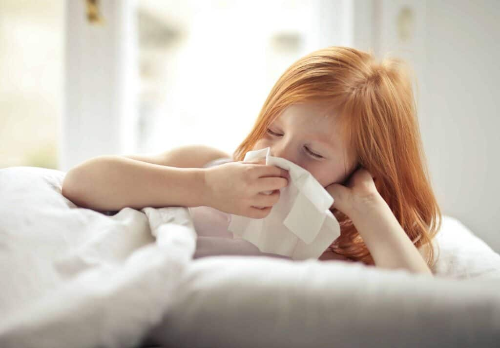 Rothaarigees Mädchen liegt im Bett und putzt sich die Nase