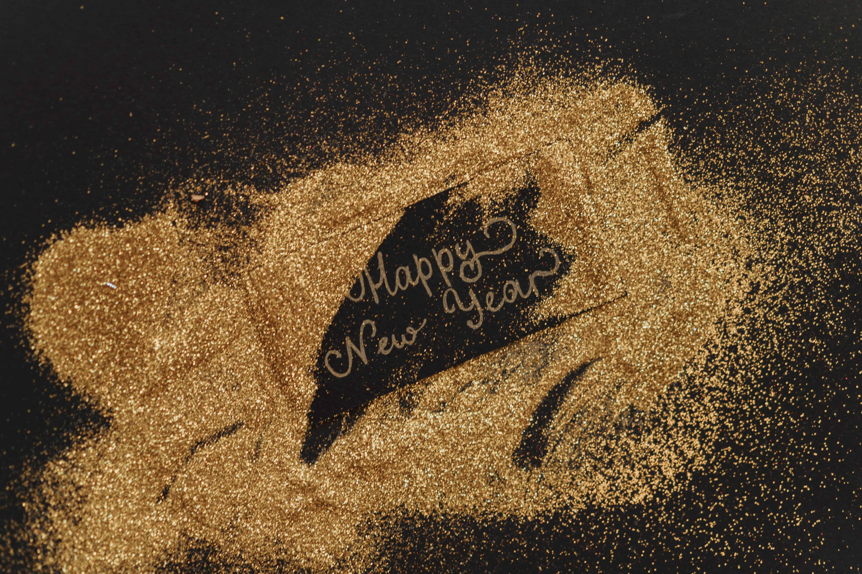 Schwarzer Hintergrund, Goldglitzer und Happy New Year in goldener Schrift