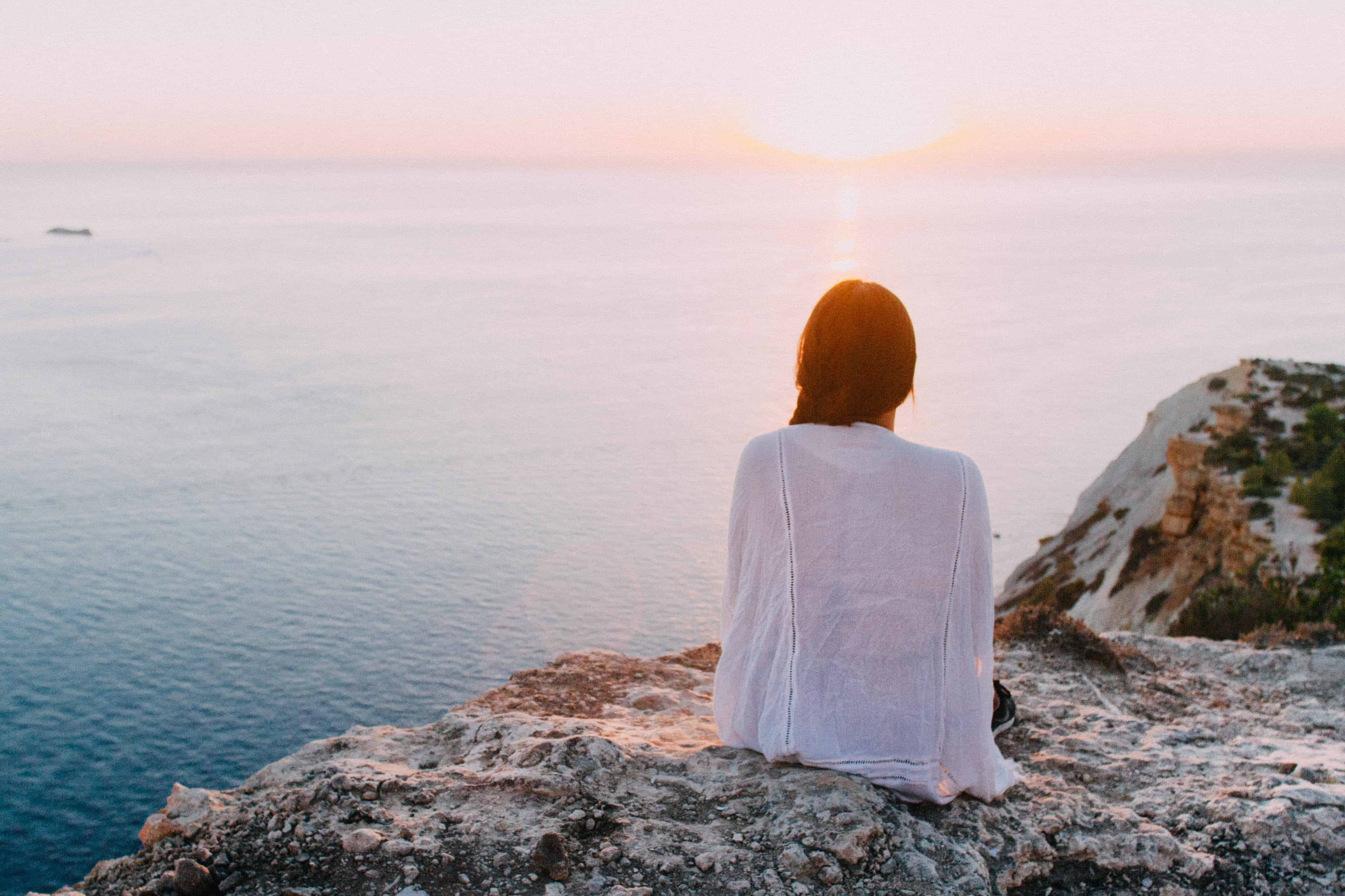 Frau sitzt auf Felsen am Wasser und sieht Sonnenuntergang