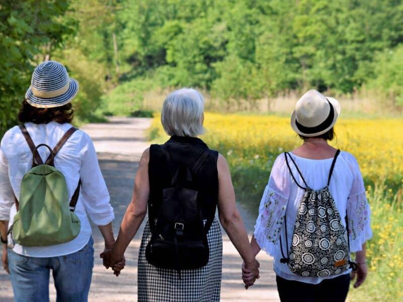 3 ältere Frauen laufen mit Rucksack einen Weg entlang