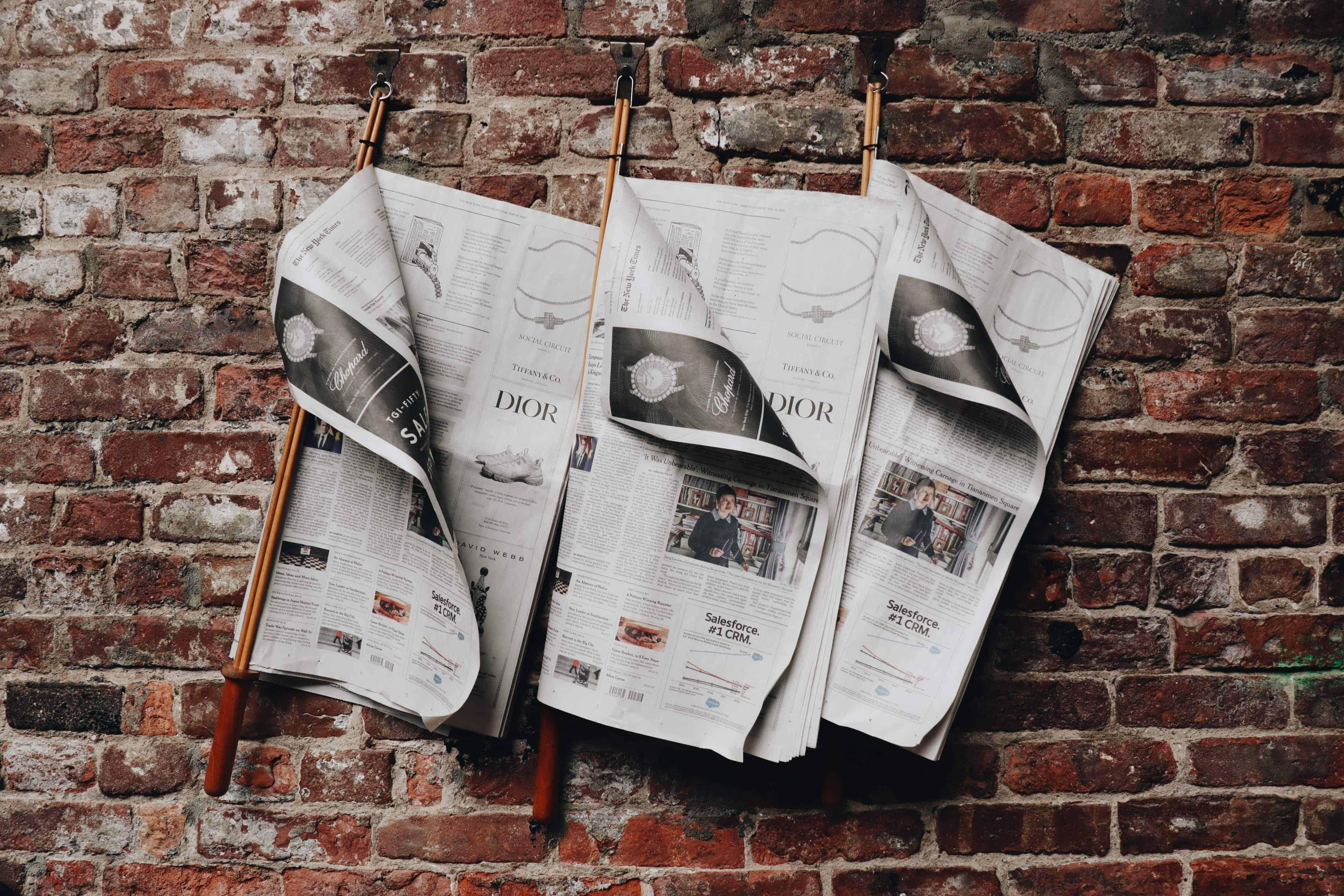 3 Zeitungen hängen an Zeitungsleser vor roter Backsteinwand