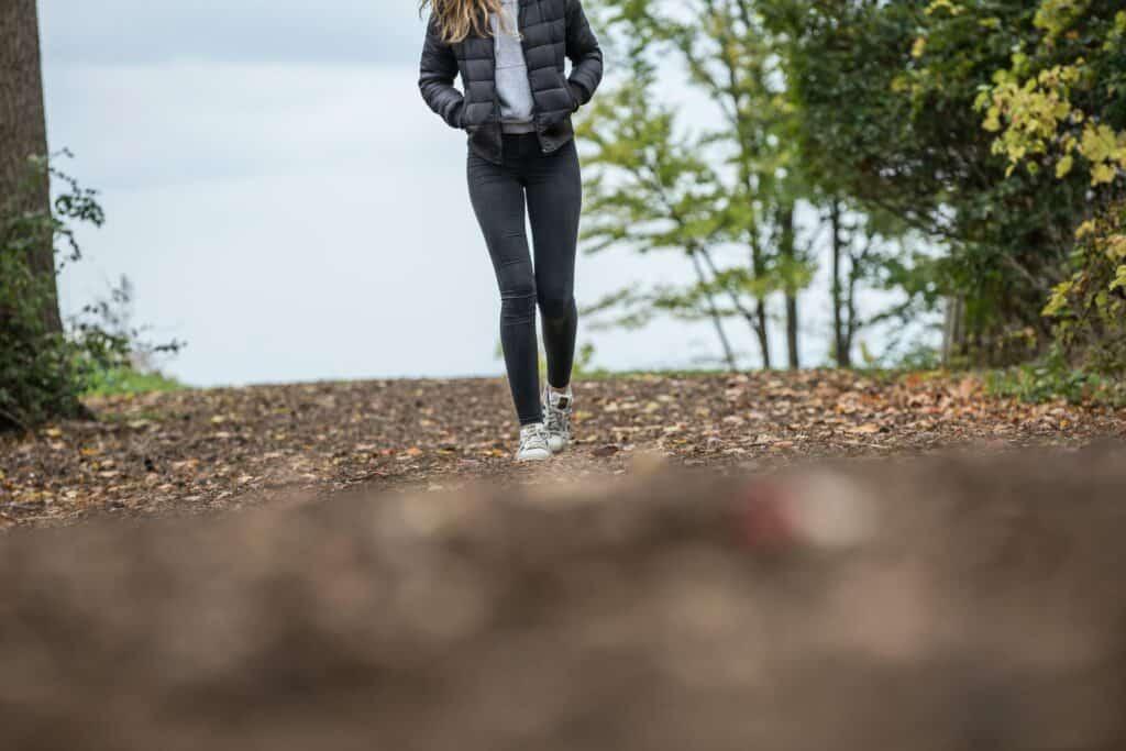 Frau läuft auf Waldboden, man sieht sie nur bis zur Schulter