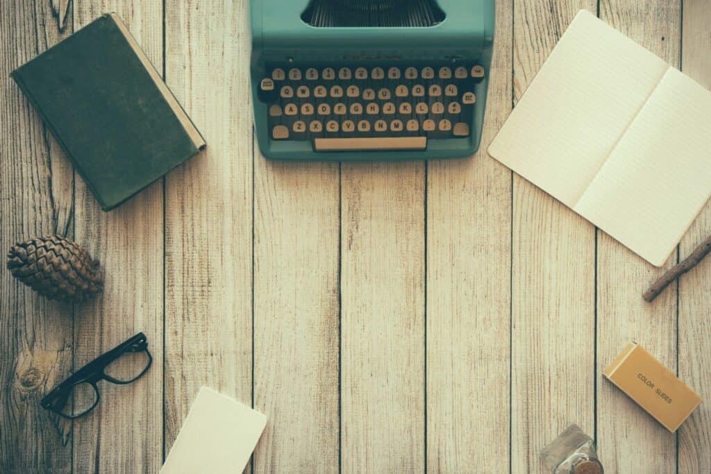 Alteschreibmaschine, Notizbuch, Brille und Tannenzapfen auf Holz