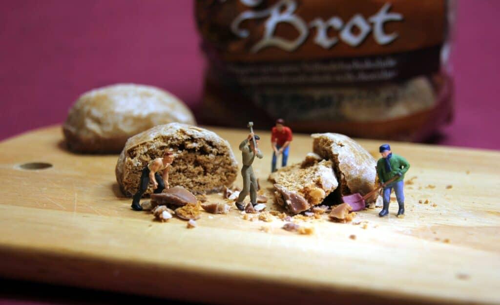 Miniaturarbeiter zerkleinern Brot auf Holzbrett
