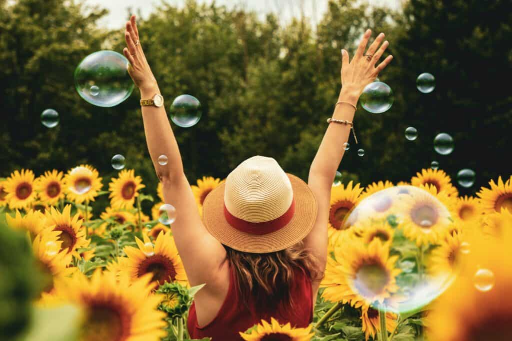 Frau von hinten mit Strohhut in Sonnenblumenfeld mit Seifenblasen