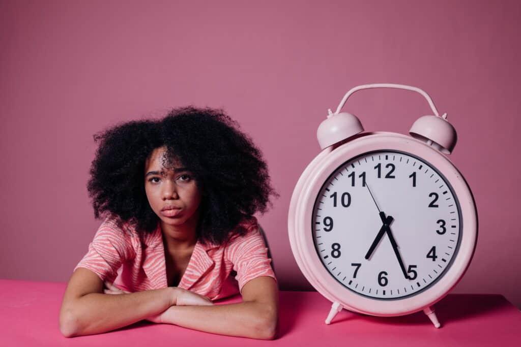 Frau sitzt neben großem rosa Wecker vor pinkem Hintergrund