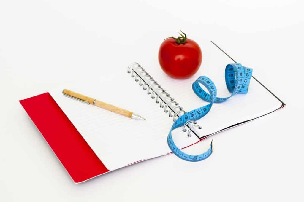 Notizbuch auf dem blaues Maßband, Tomate und Holzkugelschreiber liegen