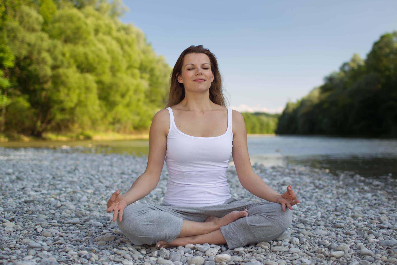 Frau meditiert auf Kieselsteinen am Fluss