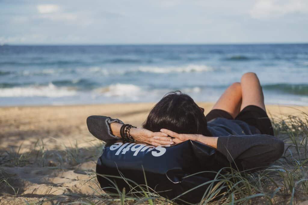 Mensch liegt am Stand und schaut aufs Meer