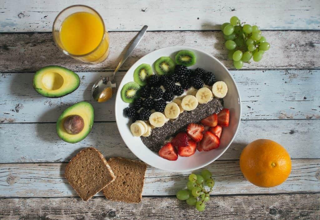Schale Obstsalat mit Löffel, Avocado, Orangensaft, Weintrauben, Orange und Vollkornbrot
