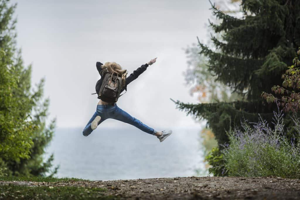 Frau mit Rucksack springt in die Luft